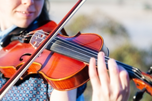 Close up detail of girl playing violin outside