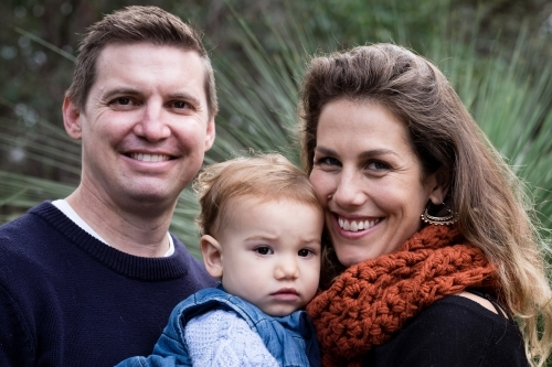 Close up Family portrait of three in bush setting looking at camera smiling