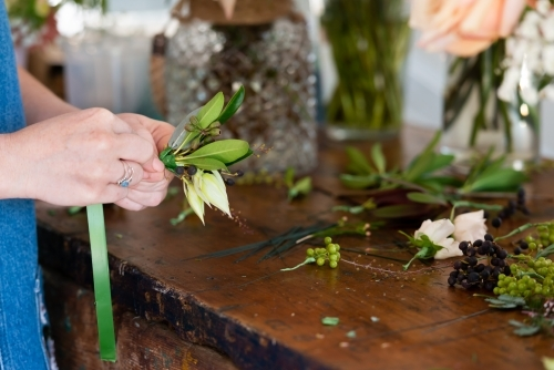 Close up of a florist preparing wedding buttonholes at a work bench