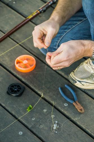 Close up of a man tying a fishing line on jetty