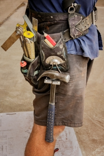 Close-up of builder wearing shorts and tool belt on construction site