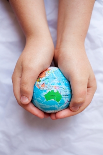 Close up of child's hands holding world globe with Australia map