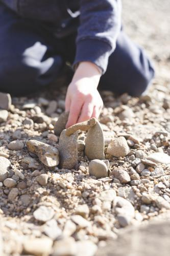 Close up of child stacking rocks