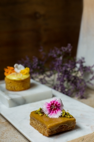 Close up of dessert cakes garnished with edible flowers