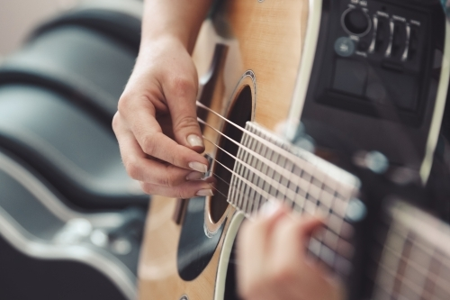 Close up of female hands playing an acoustic guitar