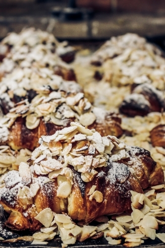 Close up of freshly baked almond croissants dusted with shaved almonds and icing sugar