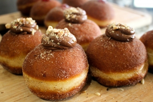 Close up of freshly baked doughnuts filled with chocolate ganache and sprinkled with hazelnuts