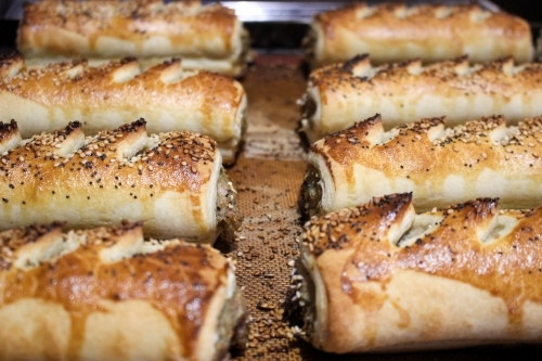Close up of freshly baked sausage rolls lined up on a baking tray