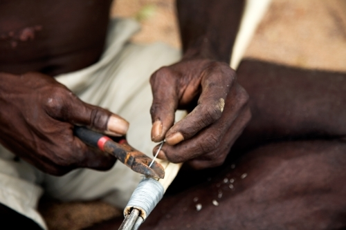 Close up of indigenous persons hands working with tools