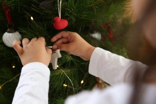Close up of little hands decorating Christmas tree