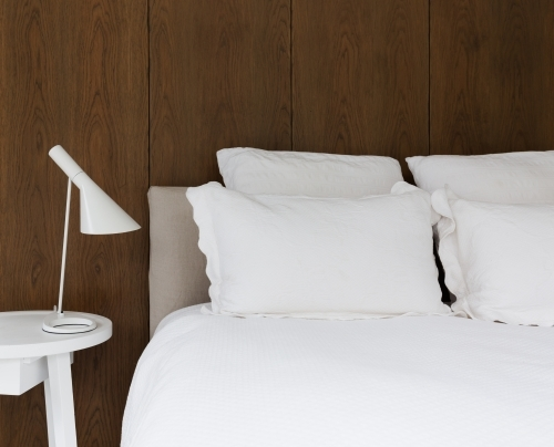 Close up of luxury white linen in bedroom with walnut lining boards on the wall behind
