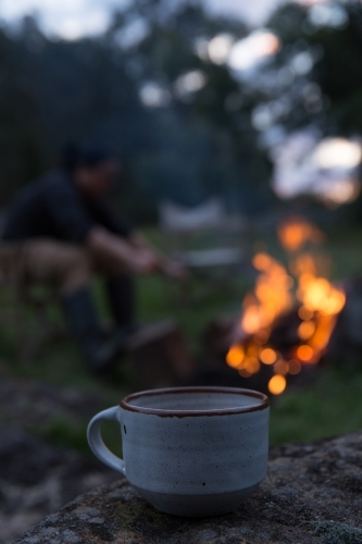Close up of mug with man tending to fire in background on rural property