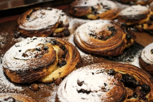 Close up of pain aux raisin pastries on baking tray dusted with icing sugar