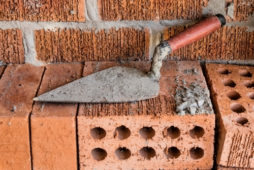 Close-up of rugged brick wall with loose bricks & trowel on building site