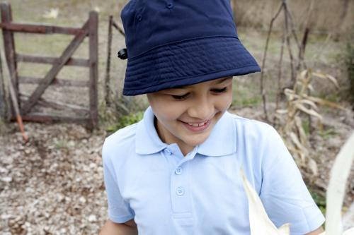 Close up of smiling boy wearing school uniform and hat outside