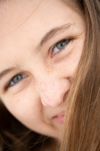 Close-up of teenage girl's face obscured by hair
