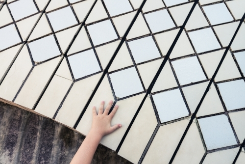 close up of tiles on Sydney Opera House with kids hand