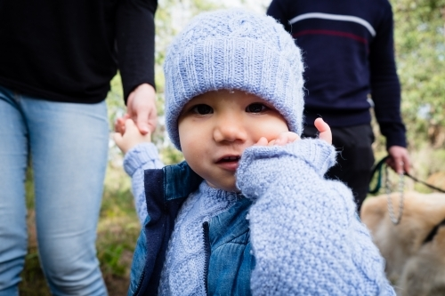 Close up of Toddler in beanie looking at camera inquisitively with parents in background