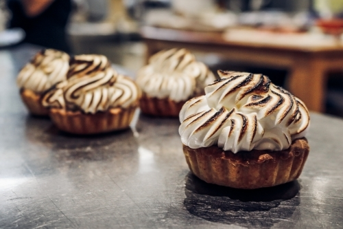 Close up of torched meringue tarts on stainless steel counter top