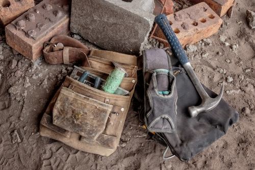 Close-up of tradesman's tool belt & tools on ground at building site