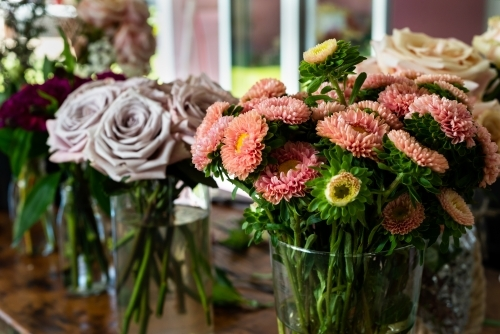 Close up of vase of orange dahlias with blurred vases of mauve and pink roses in the background