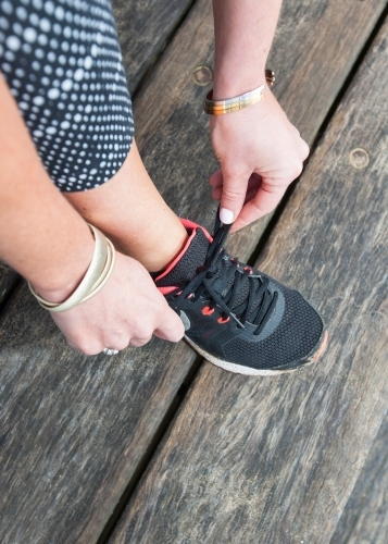 close up of woman tying her shoelace before exercising