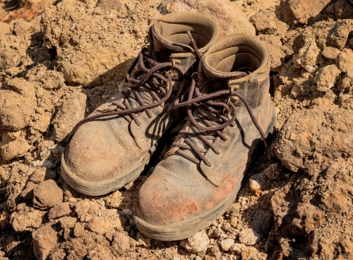 Close-up of worn leather tradesman's work boots on building site