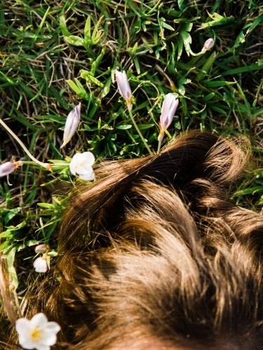 Close up of young girls hair lying in a field
