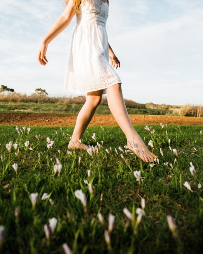 Close up of young girls legs walking in a field of flowers