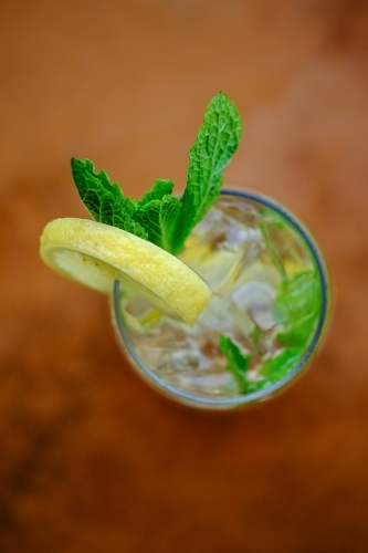 Close up overhead view of a cocktail or mocktail with ice, lemon and mint