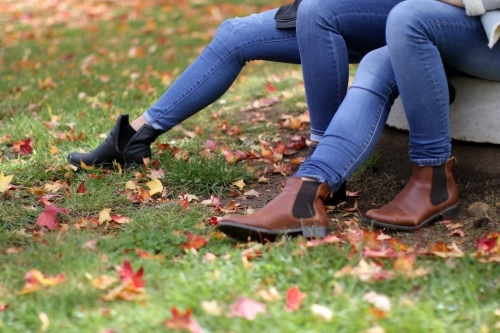 Close up shot of girls legs wearing jeans and boots surrounded by autumn leaves