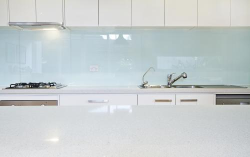 Glass kitchen splashback and white counter tops in designer home
