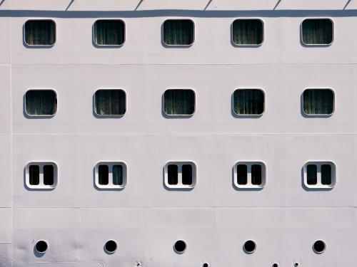 Closeup of rows of windows and portholes in a ship