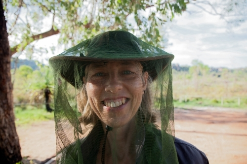 Closeup of woman smiling and wearing a fly net over her face in the outback