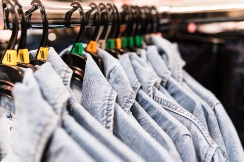 Clothing retails concept. Denim shirts on hangers in clothes store.