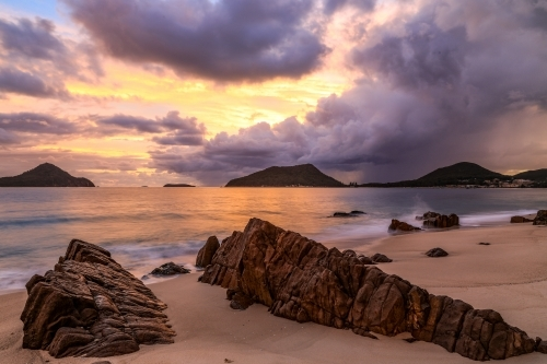 Cloudy sunrise over mountains and rocky beach