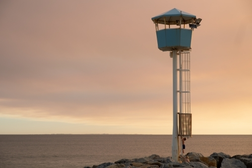 Coastal Lookout tower on groyne being climbed by young boy with dramatic sunset and ocean background