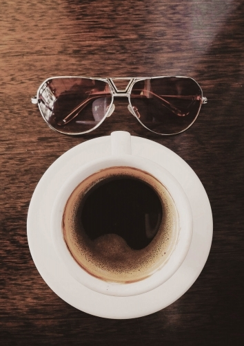 Coffee and sunglasses on table