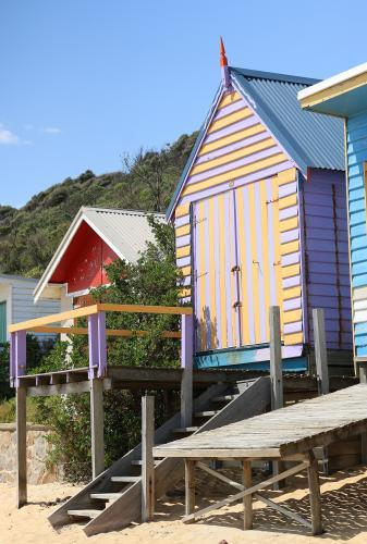Colourful beach box with stairs leading down to the sand and sea