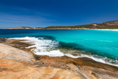 Colourful rocky foreground with waves and turquoise water and sweeping view of coastline