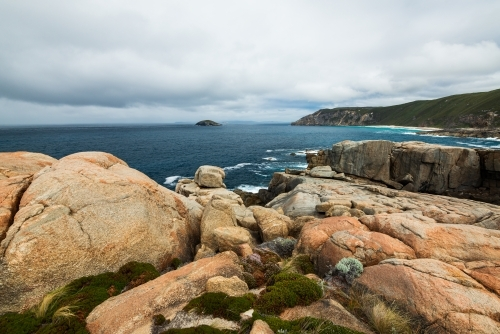 Colourful rocky foreshore on Southern Ocean with stormy sky