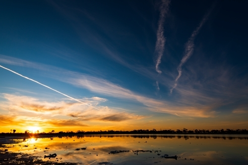 Colourful sunset over a lake with jet streams and reflections