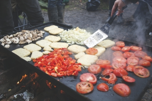 Cooking outdoor camping breakfast on campfire hot plate
