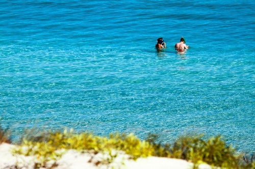 A couple in their early twenties prepare to snorkel at Coral Bay
