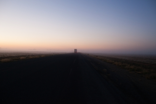 Country highway at sunrise with semi trailer truck driving off in distance