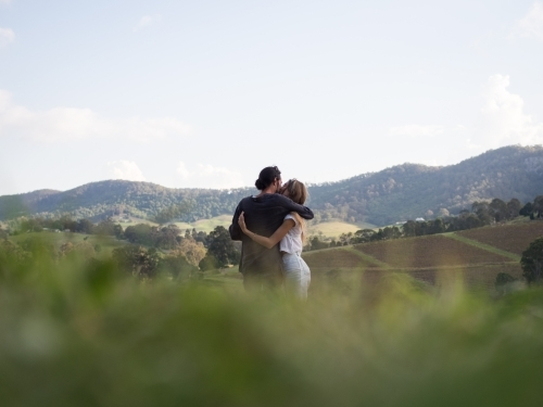 Couple cuddling whilst enjoying the view in Hunter Valley