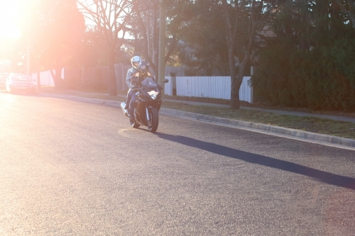 Couple riding motorbike on suburban street