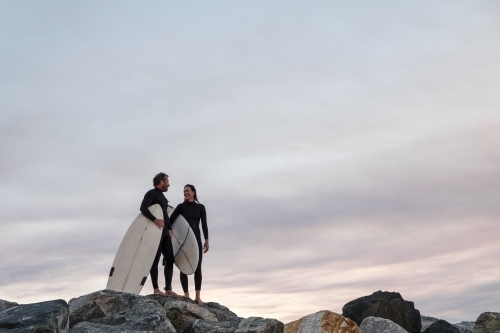 Couple standing on coastal rocks wearing wetsuits and carrying surfboards looking at sunset
