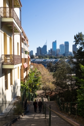 Couple walking down stairs looking to the city from Potts Point