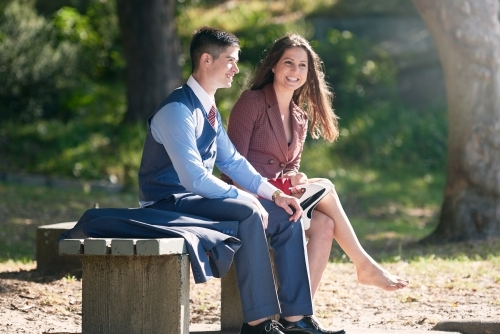 Young couple sitting on a bench in the park talking